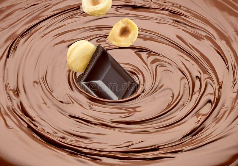 Comprimés et noisettes ou avelines en baisse en chocolat fondu photos stock