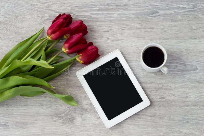 Comprim? blanc avec une tasse de caf? et de mensonges rouges de fleurs sur une table en bois blanche photos libres de droits