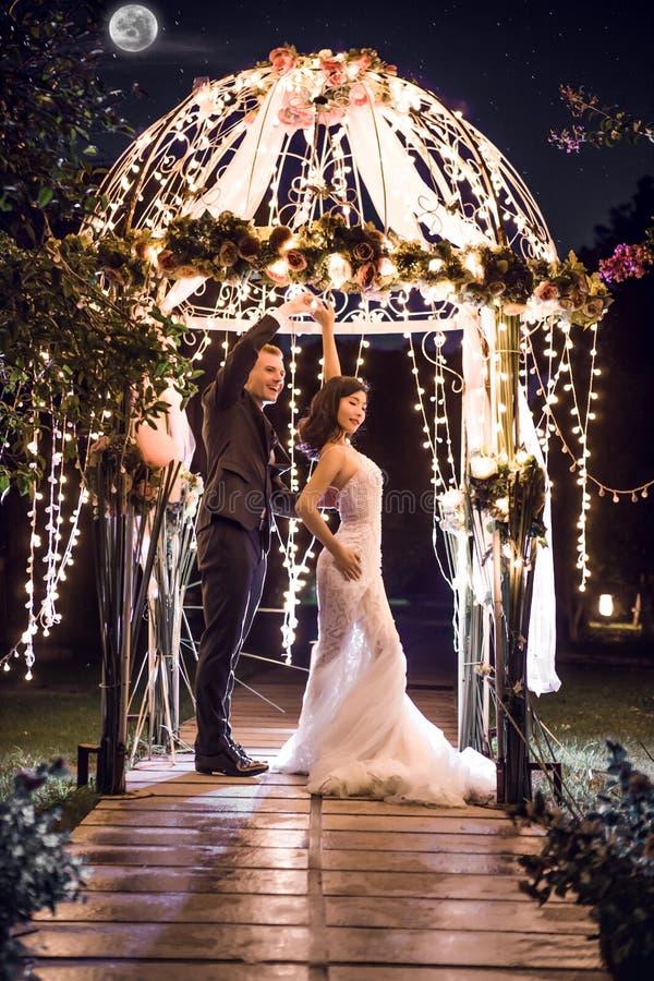 Comprimento completo da dança dos pares do casamento no miradouro iluminado na noite imagens de stock royalty free