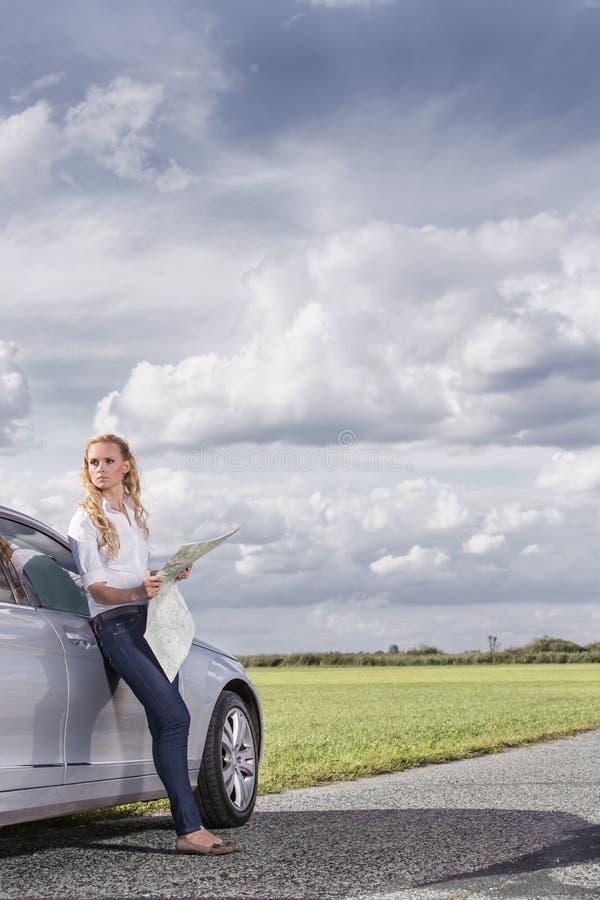Comprimento completo da mulher adulta meados de que inclina-se no carro ao guardar o mapa no campo imagem de stock
