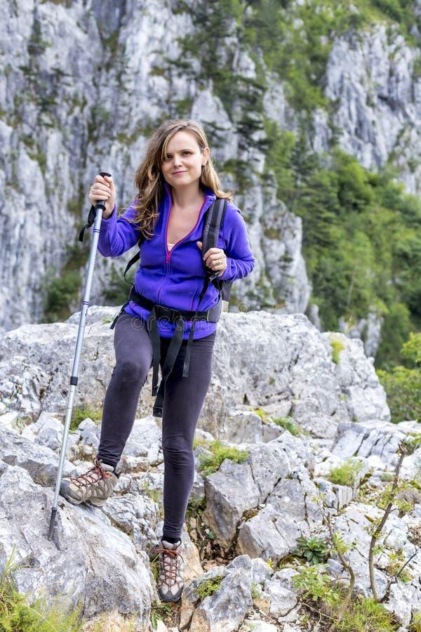 Comprimento completo da mulher bonita que guarda a caminhada do polo quando climbin foto de stock royalty free