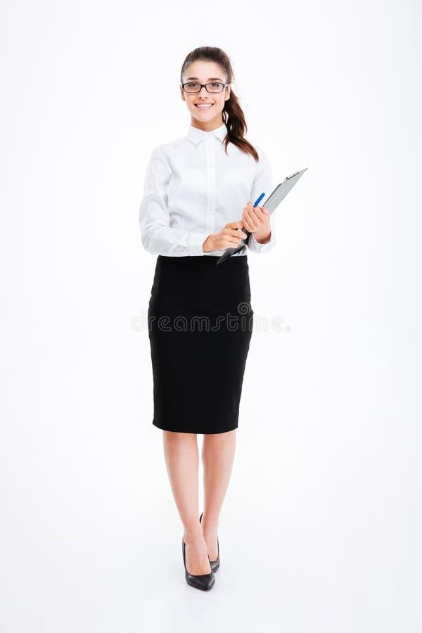 Comprimento completo da mulher de negócio alegre que está e que guarda a prancheta imagens de stock