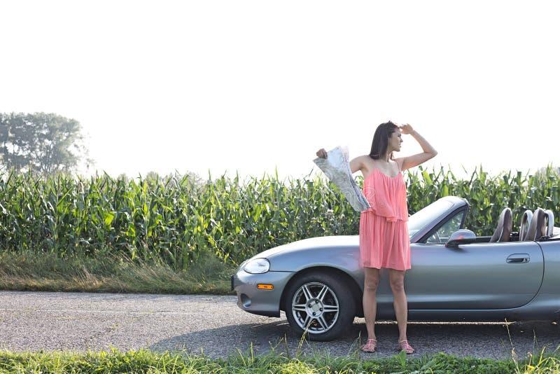 Comprimento completo da mulher que protege os olhos ao guardar o mapa pelo convertible imagem de stock royalty free