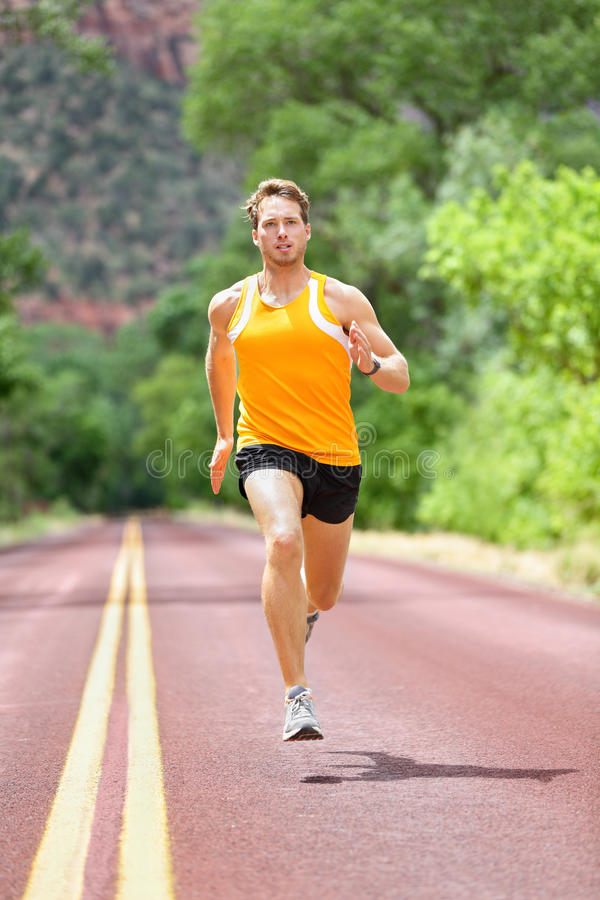 Comprimento completo de homem determinado que corre na estrada imagem de stock