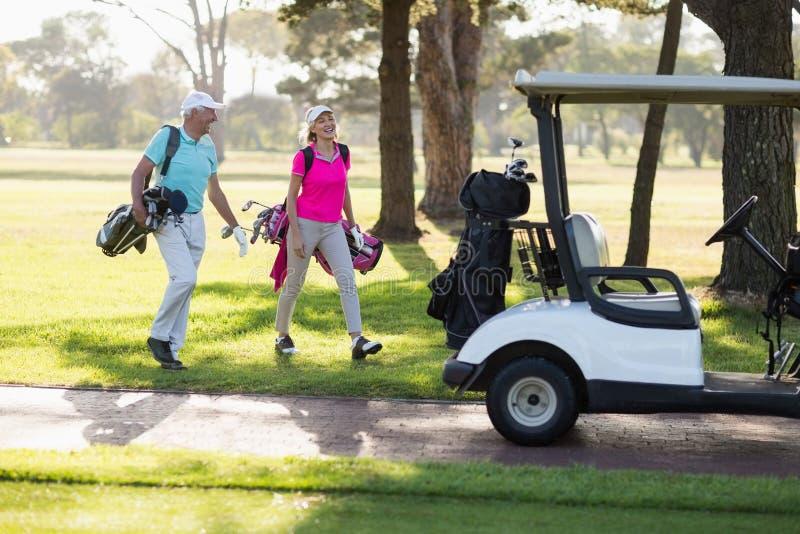 Comprimento completo de pares maduros do jogador de golfe pelo carrinho do golfe fotos de stock royalty free