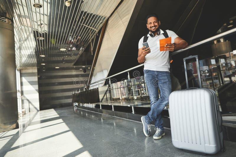 Comprimento completo de um homem hindu positivo que está no aeroporto fotos de stock
