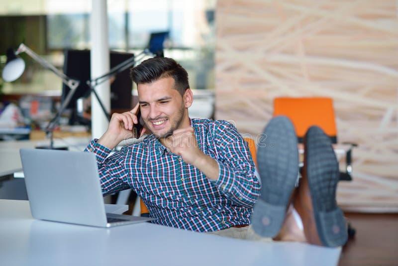 Comprimento completo de um homem de negócios novo ocasional relaxado que senta-se com pés na mesa no escritório fotografia de stock