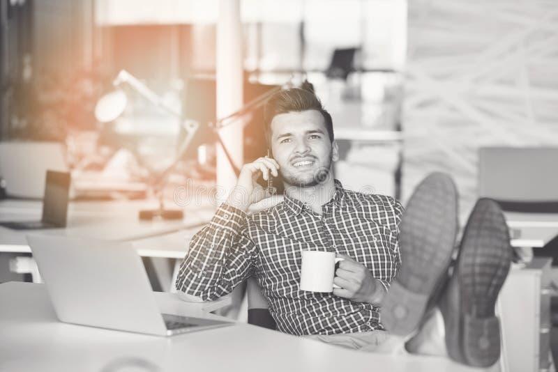 Comprimento completo de um homem de negócios novo ocasional relaxado que senta-se com pés na mesa no escritório imagens de stock royalty free
