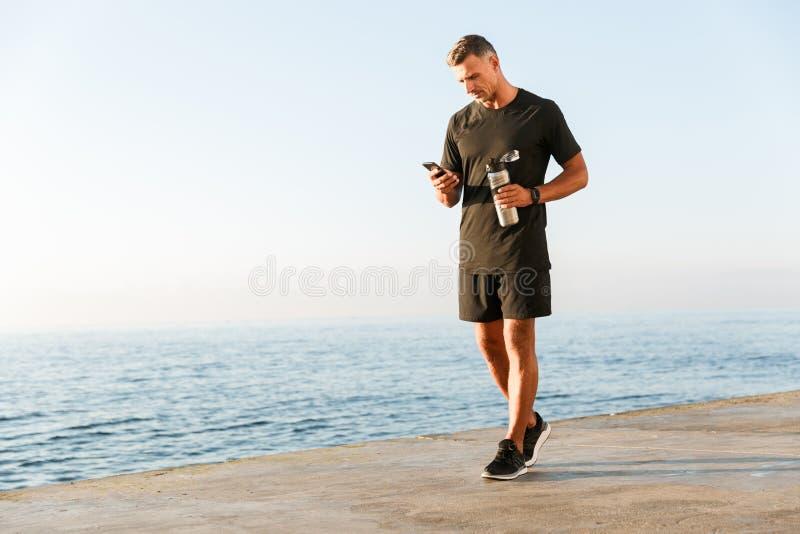 Comprimento completo do desportista de sorriso que usa o telefone celular foto de stock