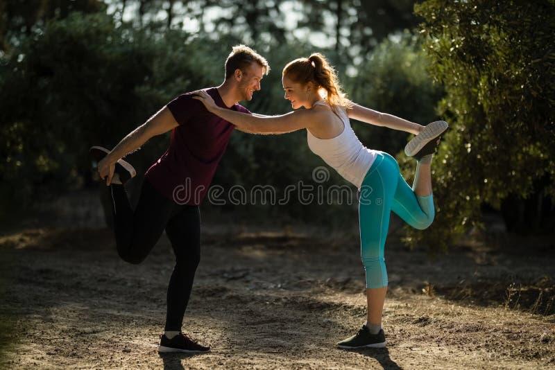 Comprimento completo do homem novo e da mulher que exercitam no campo na exploração agrícola imagem de stock royalty free