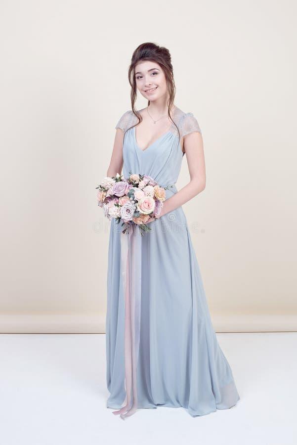 Comprimento completo do modelo fêmea bonito que guarda um ramalhete das flores que vestem no vestido laçado longo luxuoso isolado imagens de stock