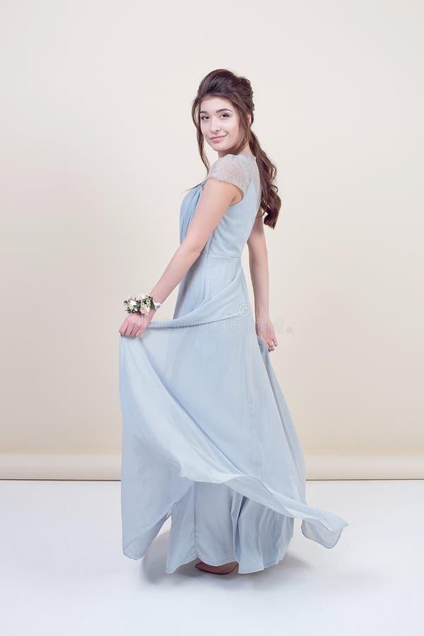 Comprimento completo do modelo fêmea bonito que guarda um ramalhete das flores que vestem no vestido laçado longo luxuoso isolado fotografia de stock royalty free