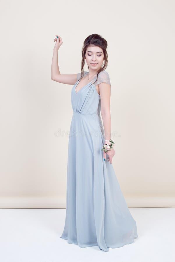 Comprimento completo do modelo fêmea bonito que guarda um ramalhete das flores que vestem no vestido laçado longo luxuoso isolado imagens de stock royalty free