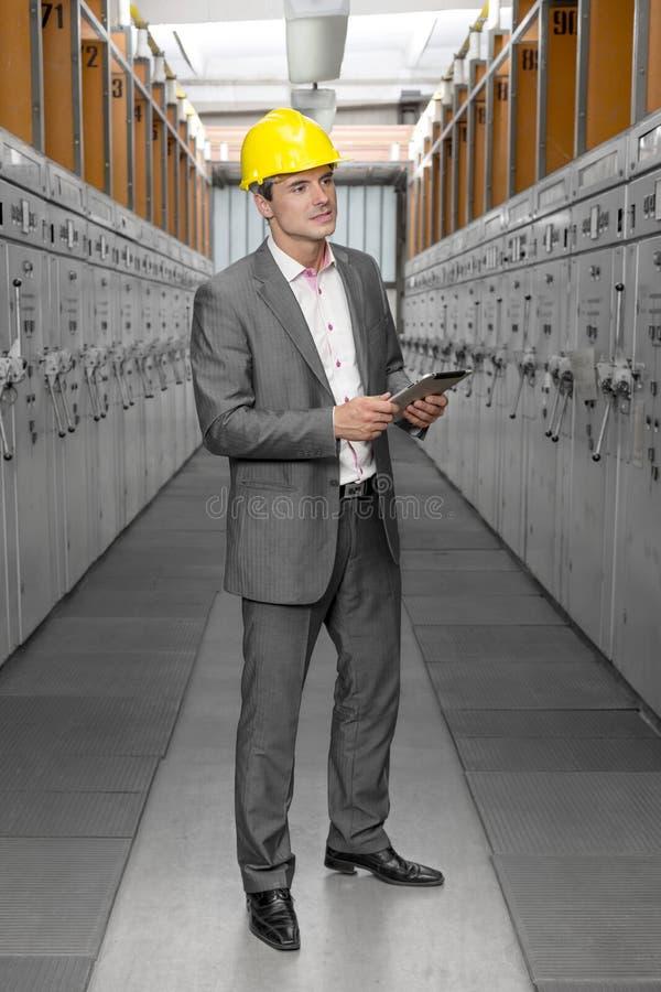Comprimento completo do supervisor masculino novo com as máquinas de exame da tabuleta digital na sala de comando fotografia de stock