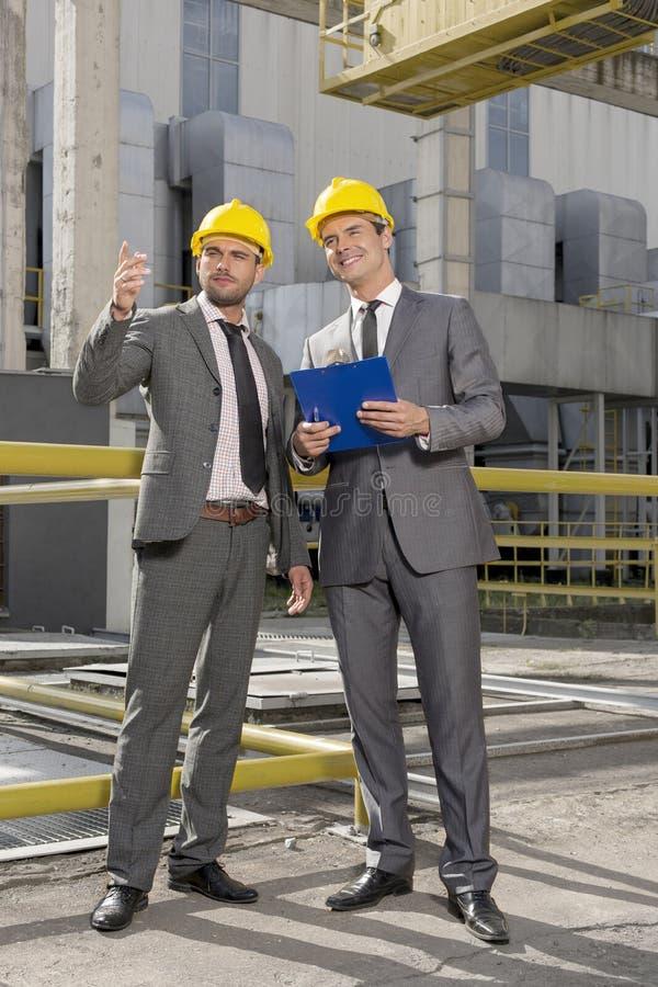 Comprimento completo dos arquitetos masculinos novos com prancheta que discutem a indústria exterior foto de stock royalty free