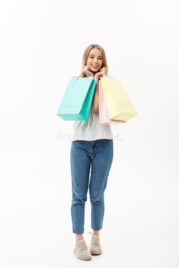 Comprimento da mulher do cliente que guardam os sacos de compras que estão o sorriso feliz e entusiasmado completos no corpo comp fotografia de stock