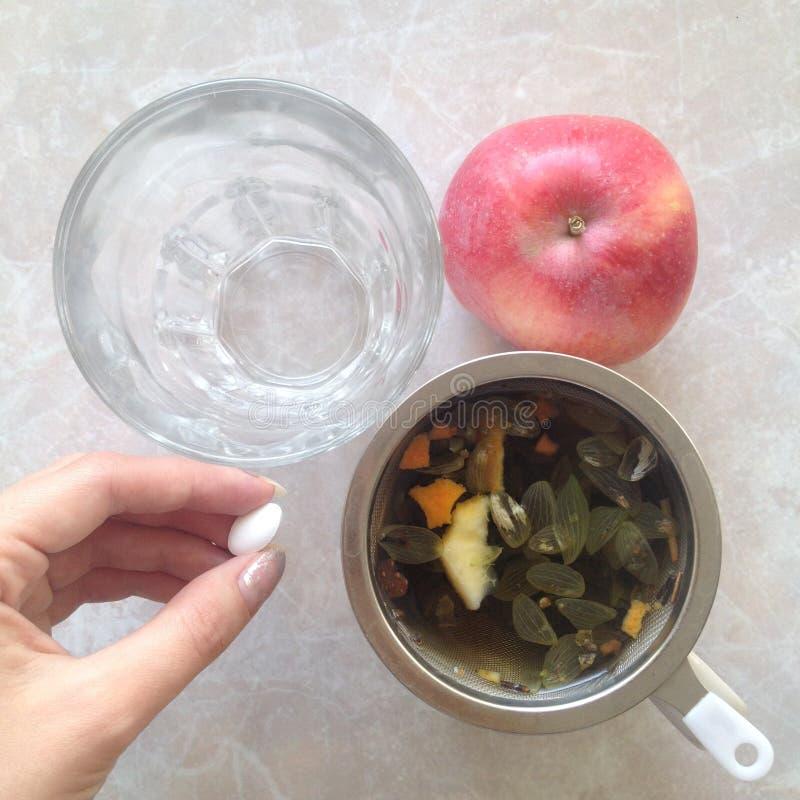 Comprimido à disposição, tisana, água e maçã vermelha Conceito dos cuidados m?dicos fotografia de stock