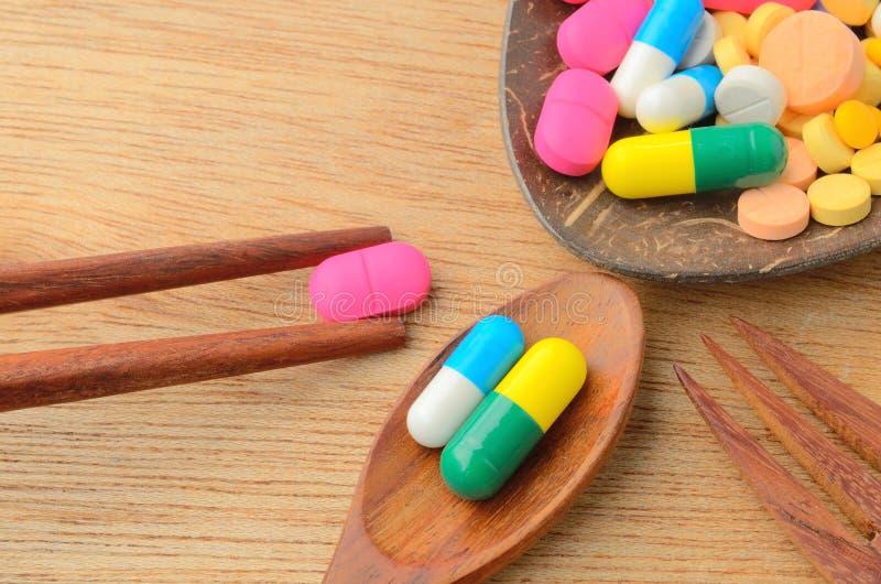 Comprimido colorido da cápsula da medicina na colher com forquilha e hashis imagem de stock