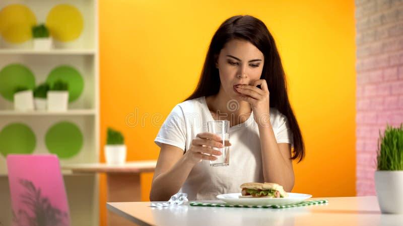 Comprimido de tomada f?mea bonito com ?gua que senta-se no restaurante do fast food, comendo demais fotos de stock