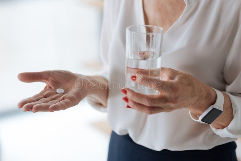 Comprimido do analgésico com um vidro da água foto de stock