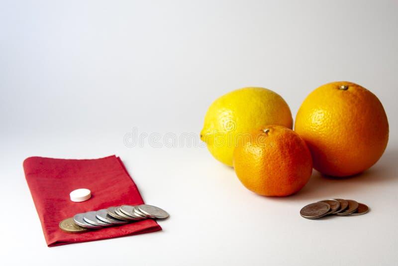 Comprimido em um serviete, em um limão, em uma laranja, em uma tanjerina e em um dinheiro vermelhos foto de stock