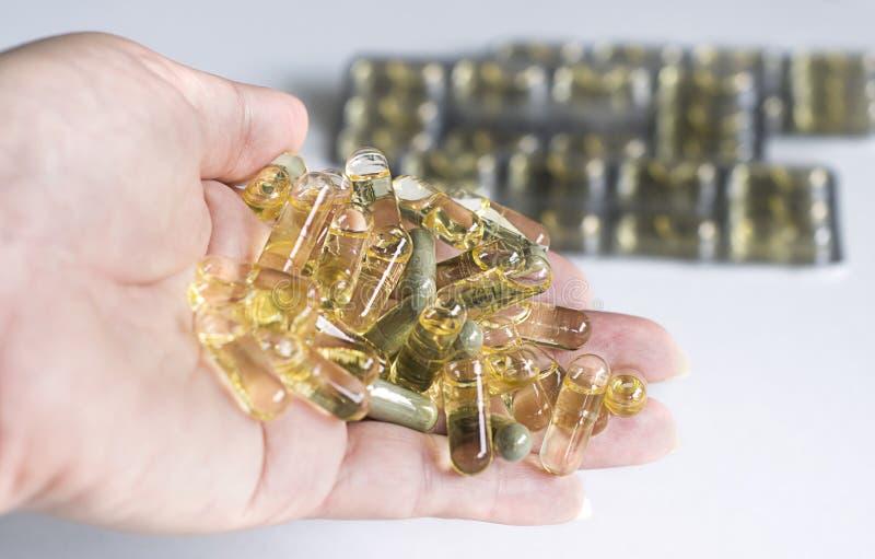 Comprimidos amarelos da cápsula em uma mão imagem de stock