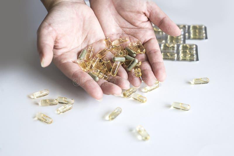 Comprimidos amarelos da cápsula no mãos fotografia de stock royalty free