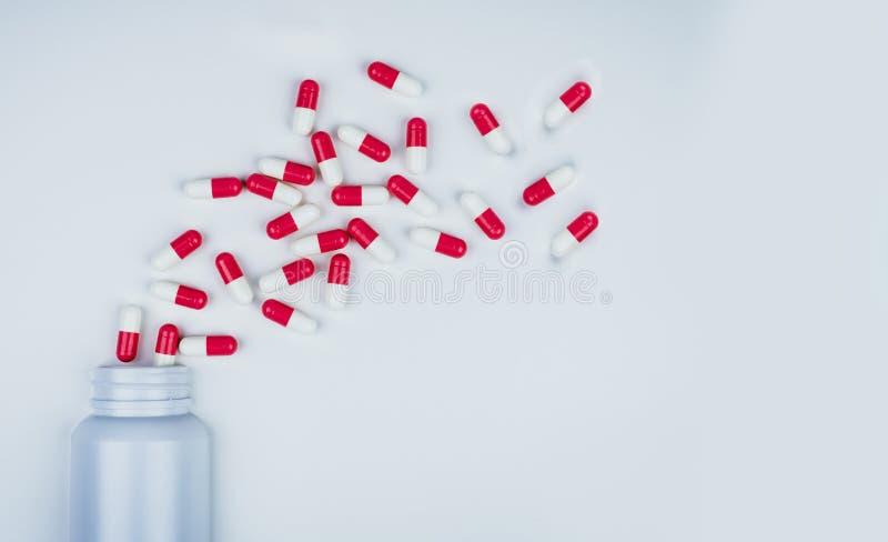 comprimidos antibióticos Vermelho-brancos da cápsula espalhados fora da garrafa plástica branca da droga Conceito da resist?ncia  foto de stock royalty free