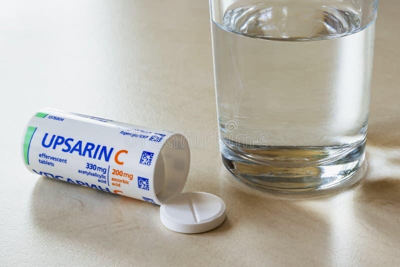 Comprimidos antipiréticos da Upsarin C e copo de água numa mesa branca aspirina efervescente solúvel com pílulas de vitamina C pa imagens de stock royalty free