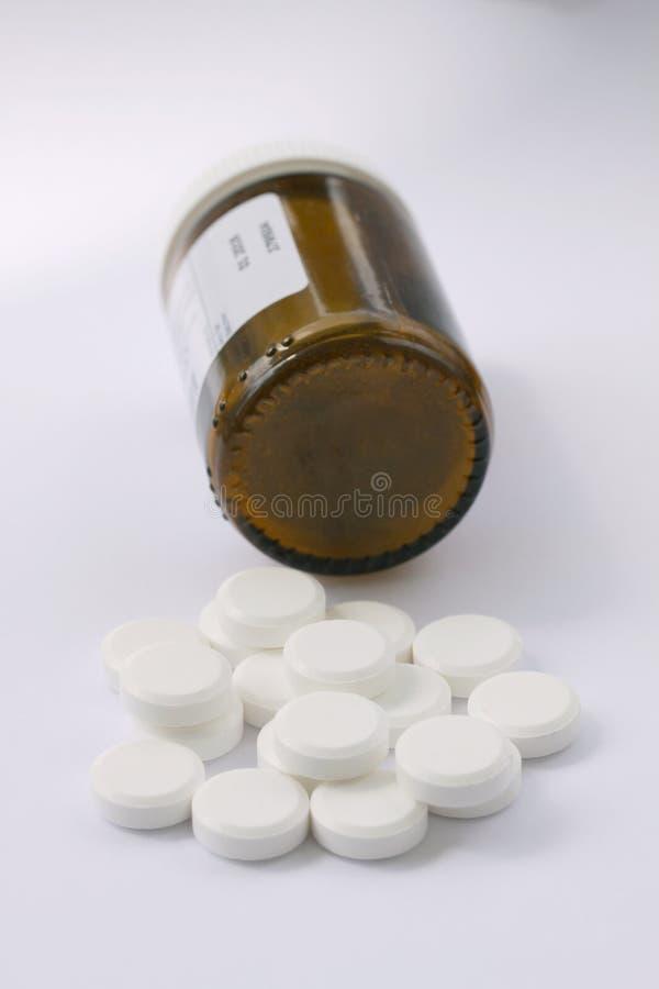 Comprimidos brancos garrafa de comprimido caída derramada Comprimidos e recipiente da medicina que encontra-se no fundo branco qu fotografia de stock