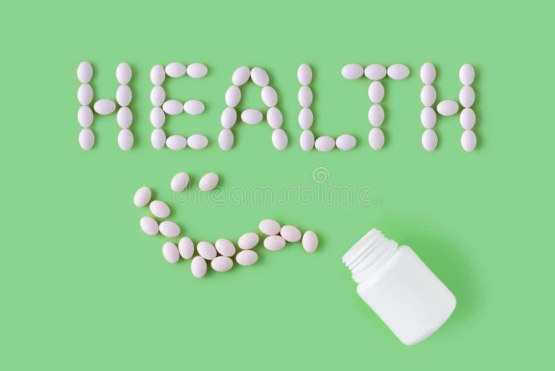 Comprimidos brancos na forma da saúde e da garrafa da palavra no fundo verde fotos de stock royalty free
