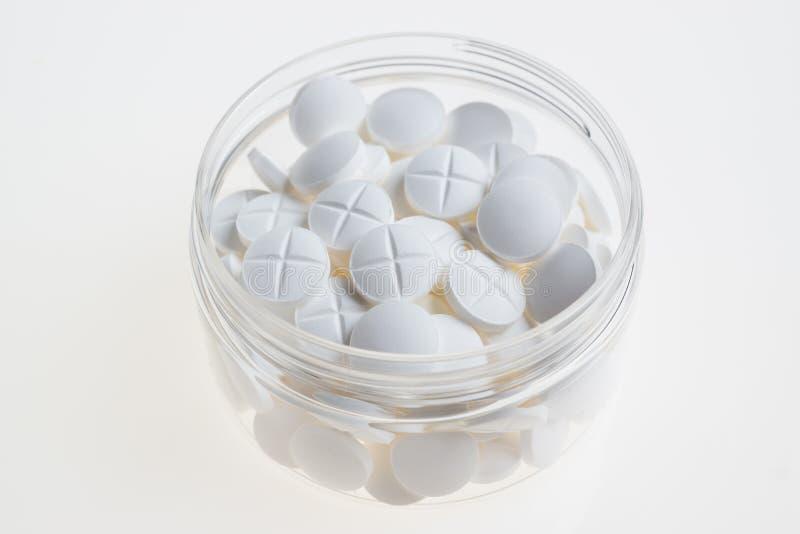 Comprimidos brancos no copo