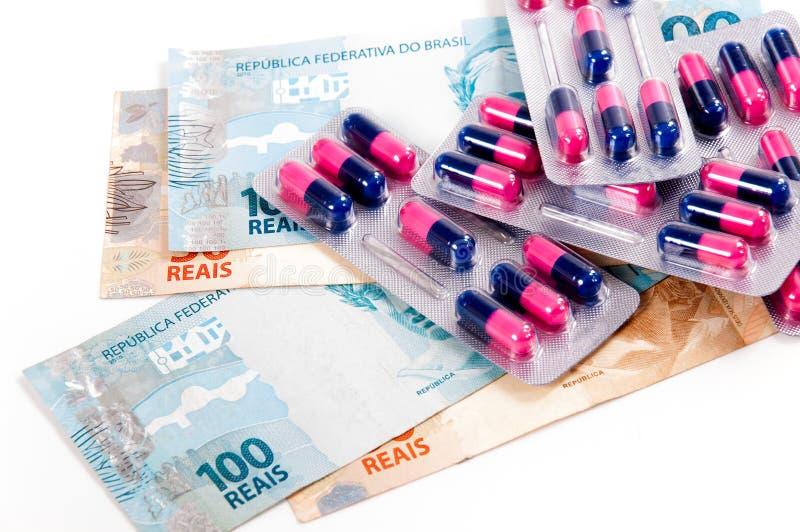 Comprimidos, cápsulas e moeda brasileira fotos de stock