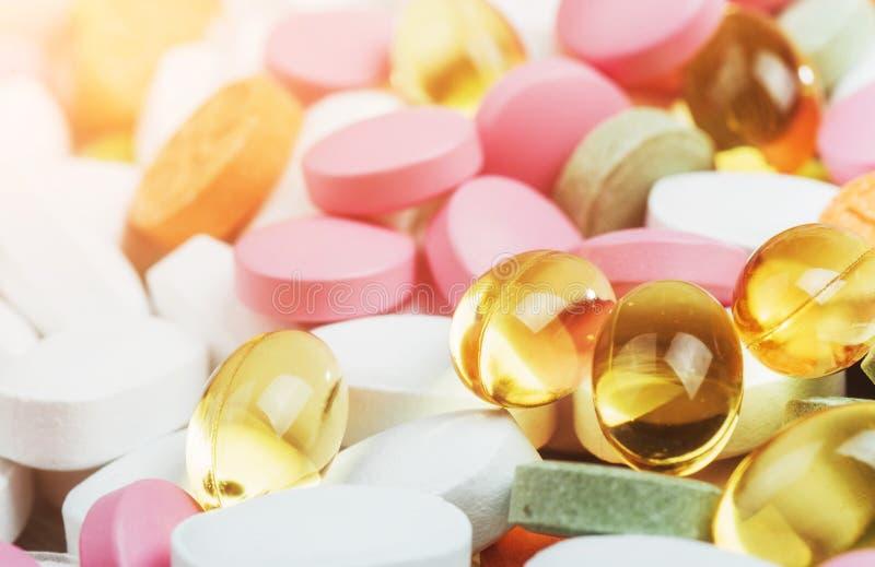 Comprimidos, cápsulas ou suplementos coloridos médicos para o tratamento e os cuidados médicos em um fundo claro imagem de stock royalty free