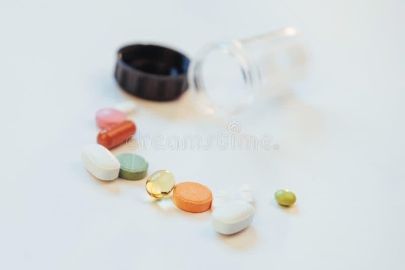 Comprimidos, cápsulas ou suplementos coloridos médicos para o tratamento e os cuidados médicos em um fundo claro imagens de stock