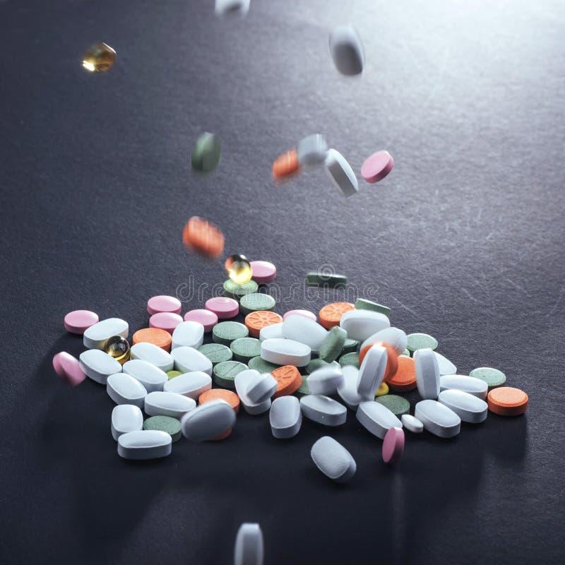 Comprimidos, cápsulas ou suplementos coloridos médicos para o tratamento e os cuidados médicos em um fundo preto imagem de stock royalty free
