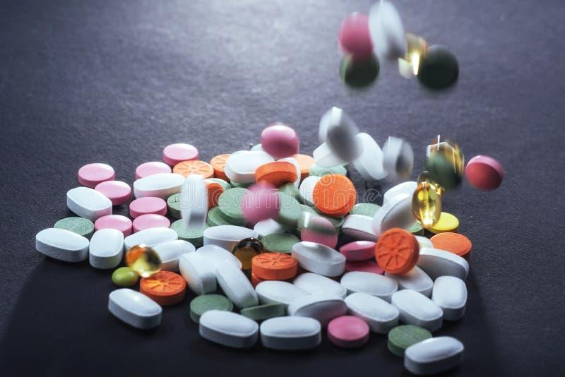 Comprimidos, cápsulas ou suplementos coloridos médicos para o tratamento e os cuidados médicos em um fundo preto fotos de stock royalty free