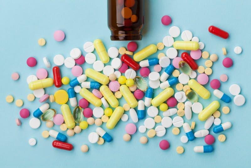 Comprimidos coloridos da droga no fundo azul, conceito farmacêutico foto de stock royalty free