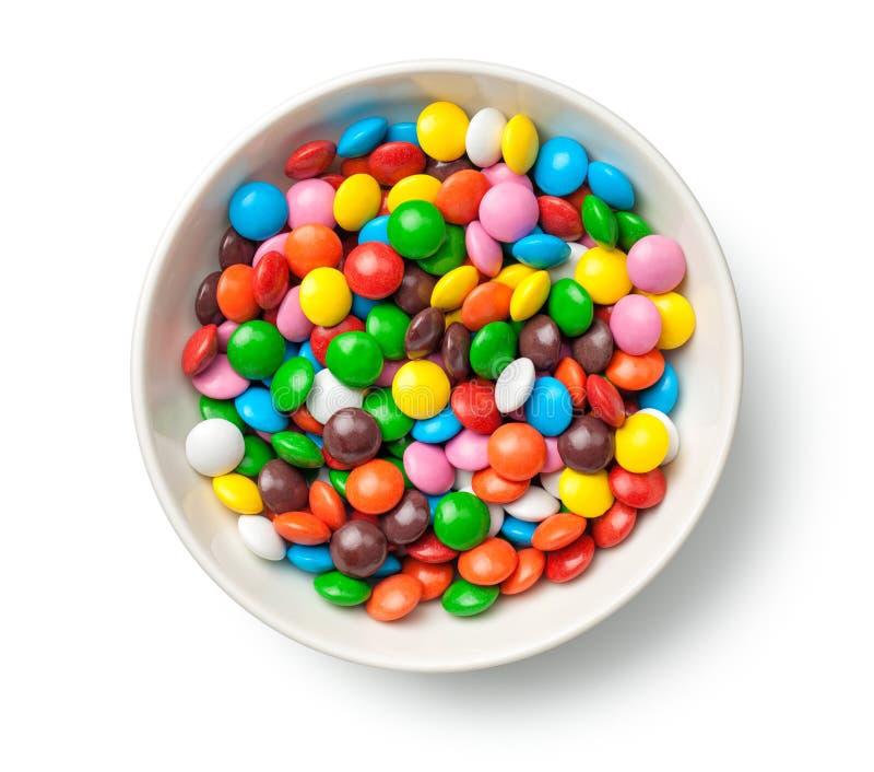Comprimidos coloridos dos doces de chocolate na bacia isolada em Backgro branco imagem de stock