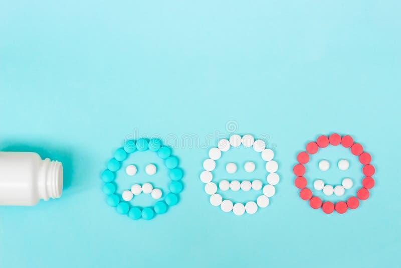 Comprimidos coloridos e caras engraçadas e uma garrafa plástica em um fundo azul O conceito dos antidepressivos e da cura imagens de stock royalty free