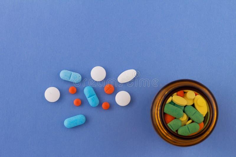 Comprimidos coloridos em um claro - fundo azul ao lado de uma garrafa de vidro que contém drogas imagem de stock royalty free