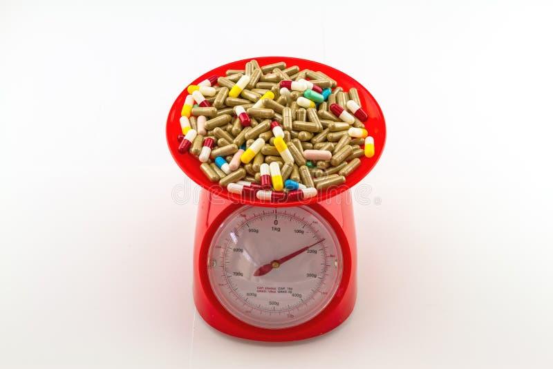 Comprimidos coloridos na escala vermelha do peso imagens de stock royalty free