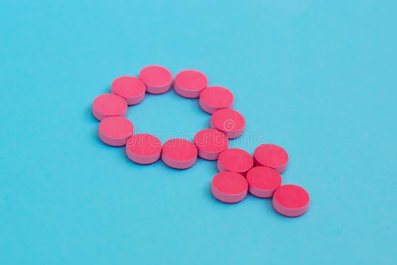 Comprimidos contraceptivos como o símbolo do gênero no fundo azul Terapia fêmea da hormona imagens de stock