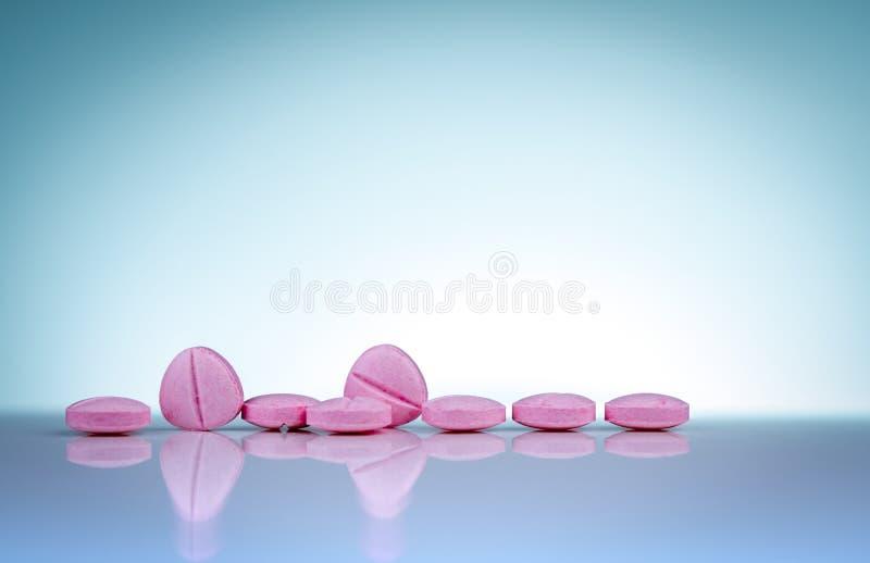 Comprimidos cor-de-rosa das tabuletas com sombra no fundo do inclina??o Ind?stria farmac?utica Produtos da farm?cia Vitaminas e s foto de stock