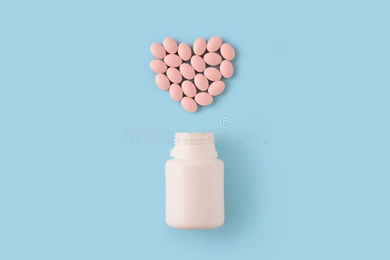 Comprimidos cor-de-rosa na forma do coração e da garrafa no fundo azul fotos de stock royalty free