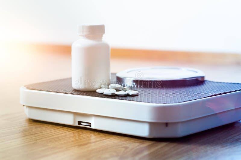Comprimidos da dieta em uma escala Medicina da perda de peso imagem de stock