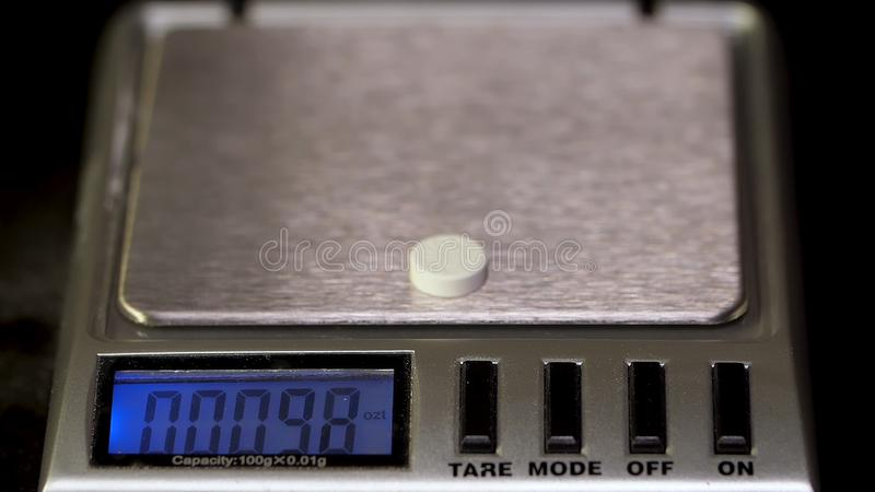 Comprimidos da dieta em uma escala Medicina da perda de peso derramada Tabuleta nas escalas para que a medida exata do peso evite fotografia de stock royalty free