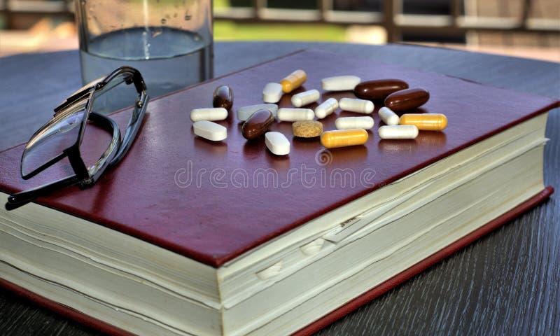 Comprimidos da medicina ou comprimidos da droga no livro foto de stock royalty free