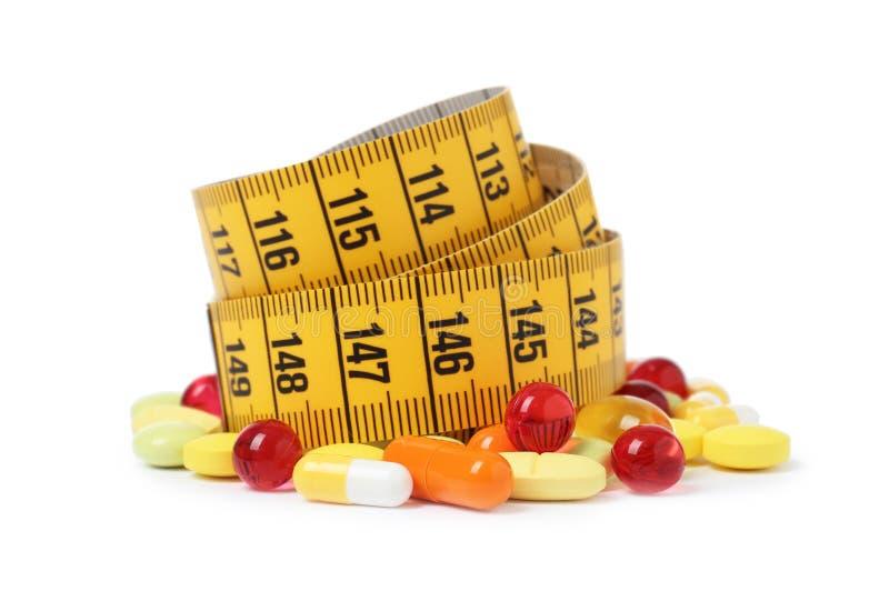 Comprimidos da perda de peso e fita de medição imagens de stock