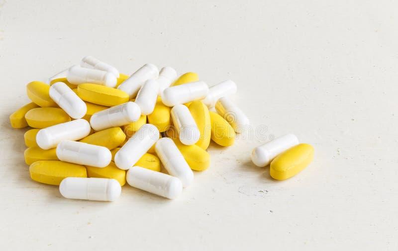 Comprimidos da vitamina que encontram-se em uma placa de madeira pintada imagem de stock